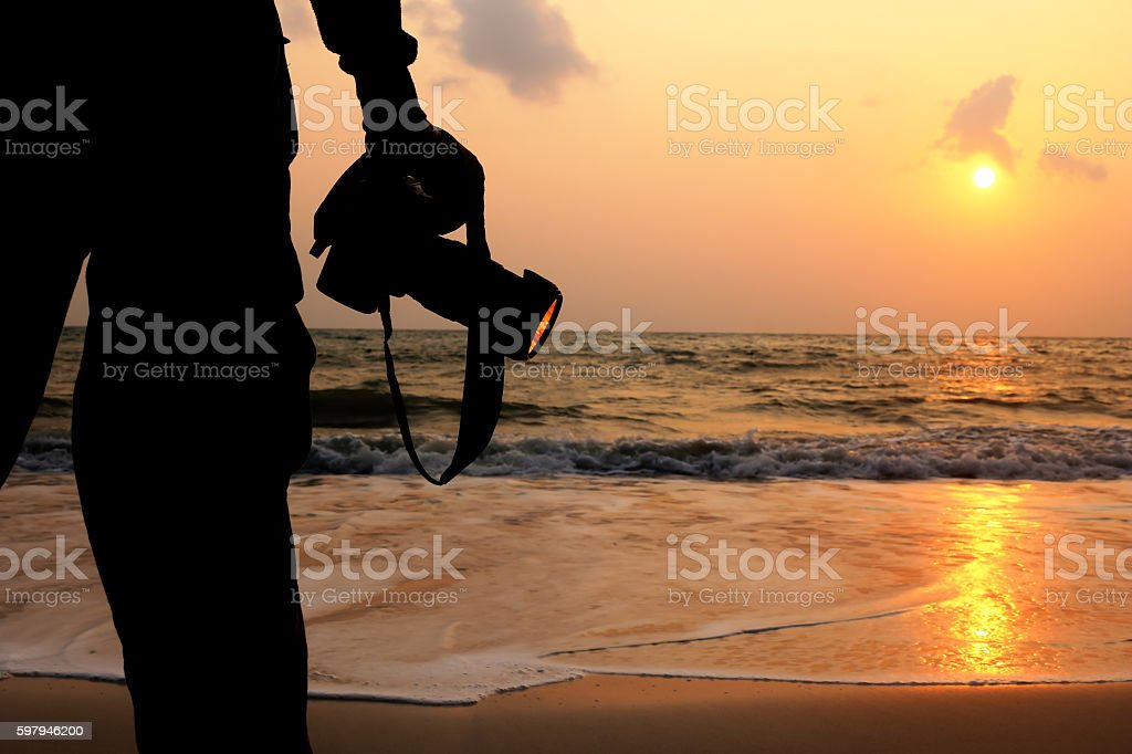Man with camera on the beach. stock photo