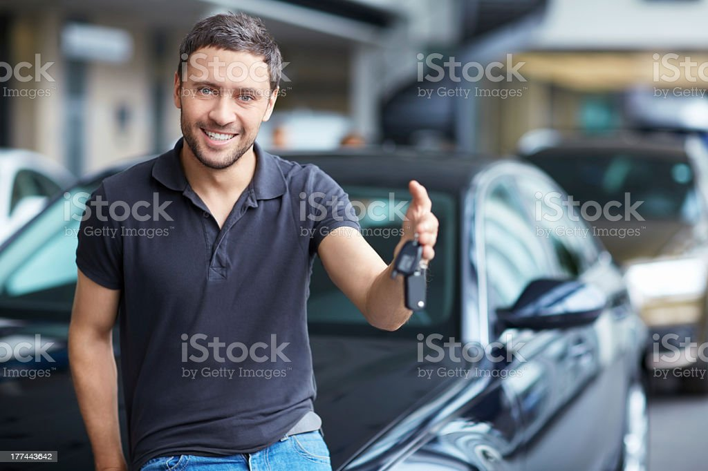 Man with car keys leaning on new car stock photo