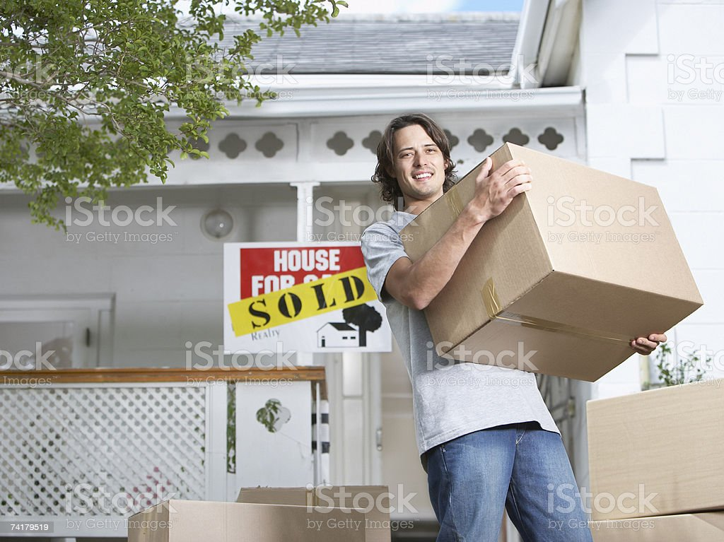 Man with cardboard boxes standing in front of house with sold sign royalty-free stock photo