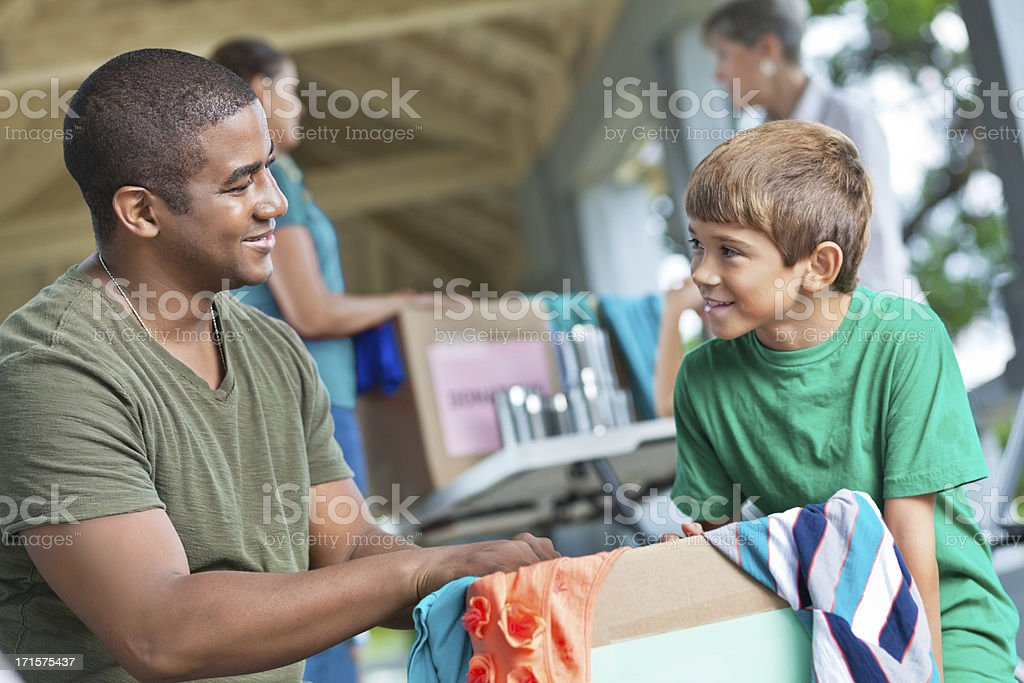 Man with child volunteering at clothes and food donation place stock photo