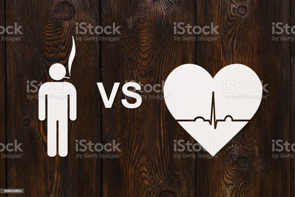 Man with cigarette and heart with echocardiogram. Quit smoking concept stock photo