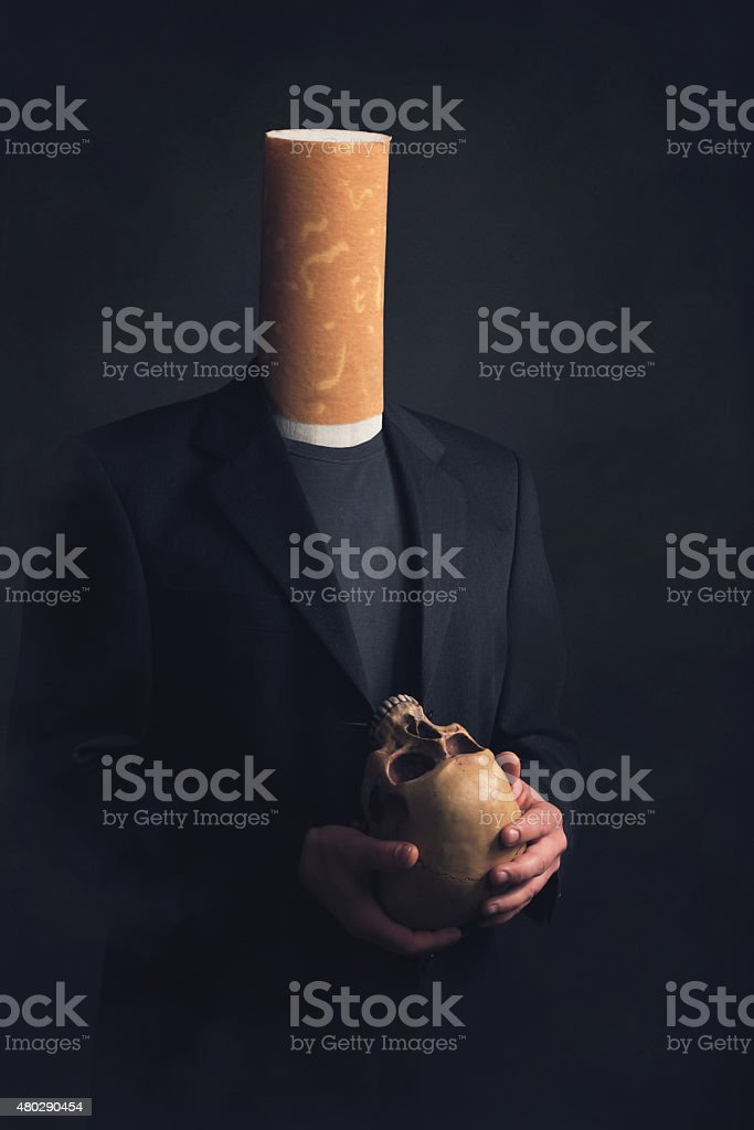 Man with cigarette filter as head holding a skull stock photo