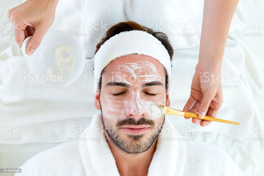 Man with clay facial mask in beauty spa. stock photo