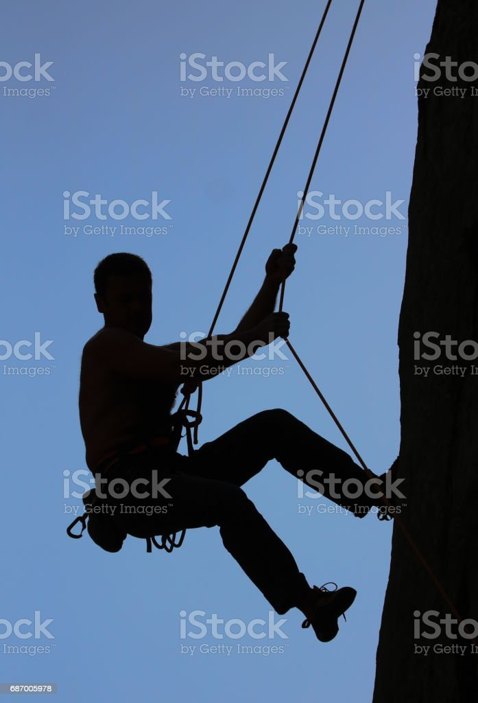 Man with climbing equipment rock climbing and overhanging. stock photo