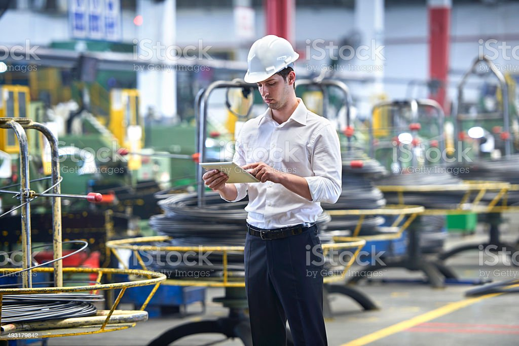 Man with clipboard in factory stock photo