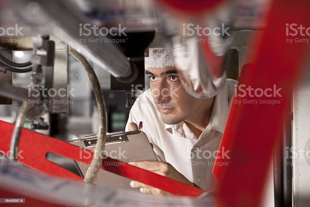 Man with clipboard looking through machine royalty-free stock photo