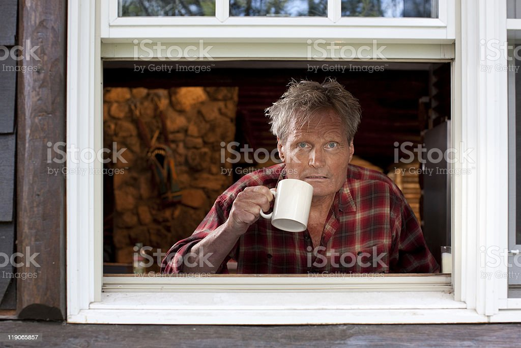 Man With Coffee Cup Looking Out of Window royalty-free stock photo
