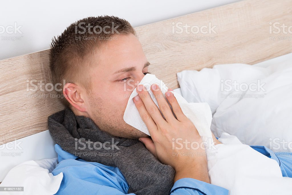Man With Cold Blowing Her Nose stock photo