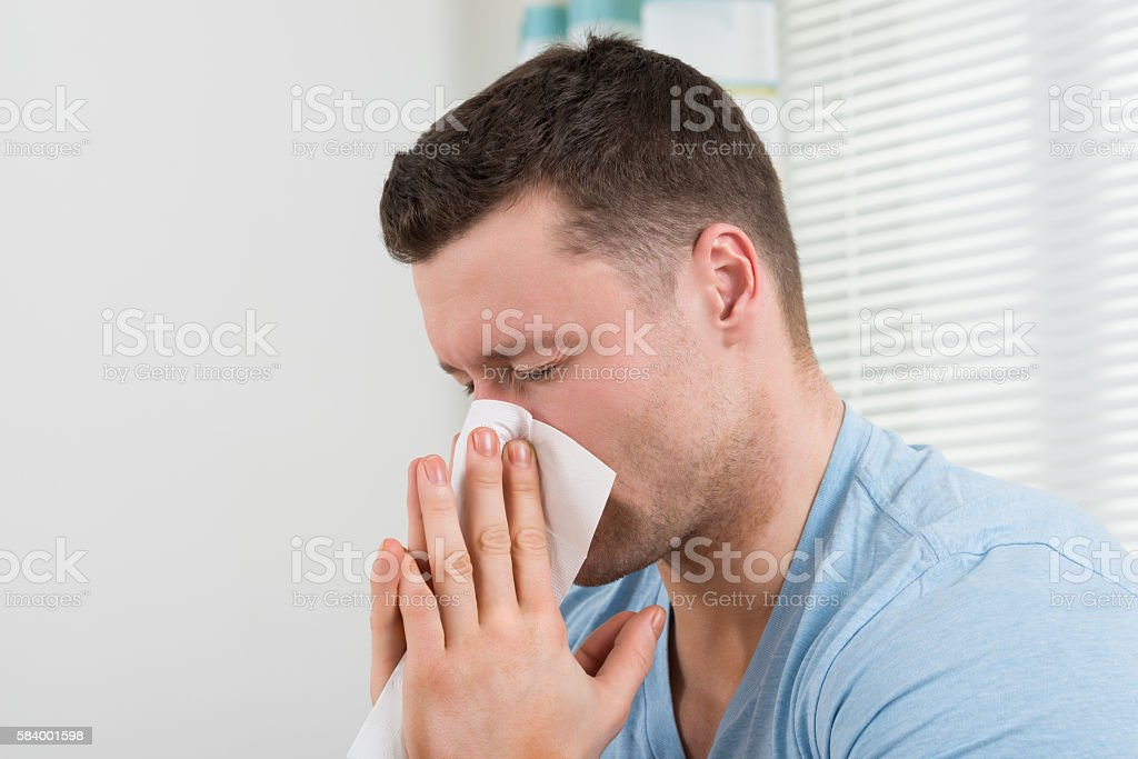 Man With Cold Blowing His Nose At Home stock photo