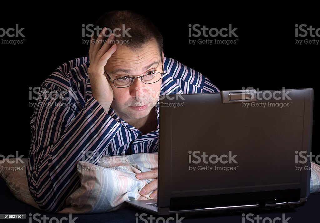 man with computer in bed stock photo