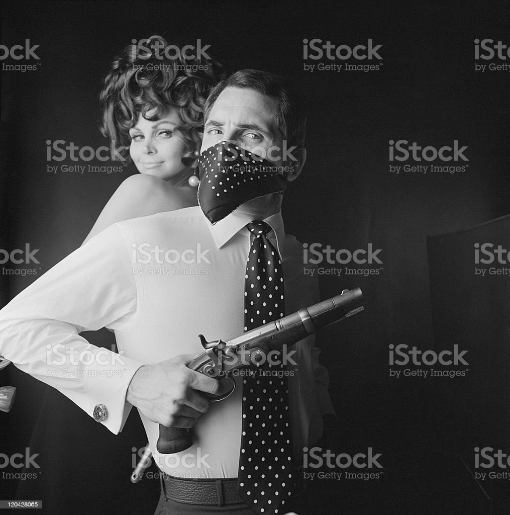 Man with covered mouth holding gun and woman smiling at him royalty-free stock photo