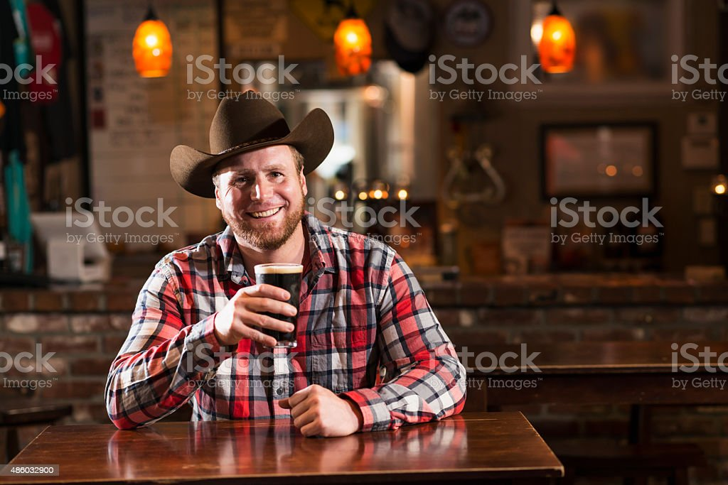 Man with cowboy hat sitting in bar drinking beer stock photo