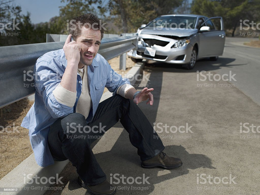 Man with crashed car calling for roadside assistance, royalty-free stock photo