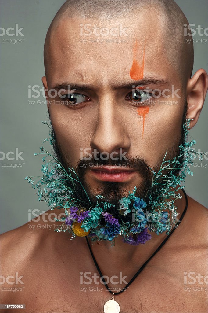 Man with creative makeup and flowers in his beard royalty-free stock photo