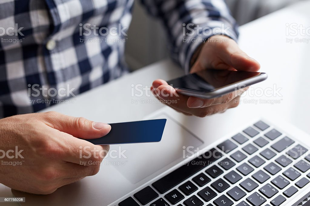 Man with credit card and phone when paying online stock photo