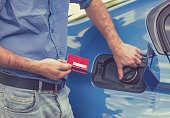 Man with credit card opening fuel tank of new car