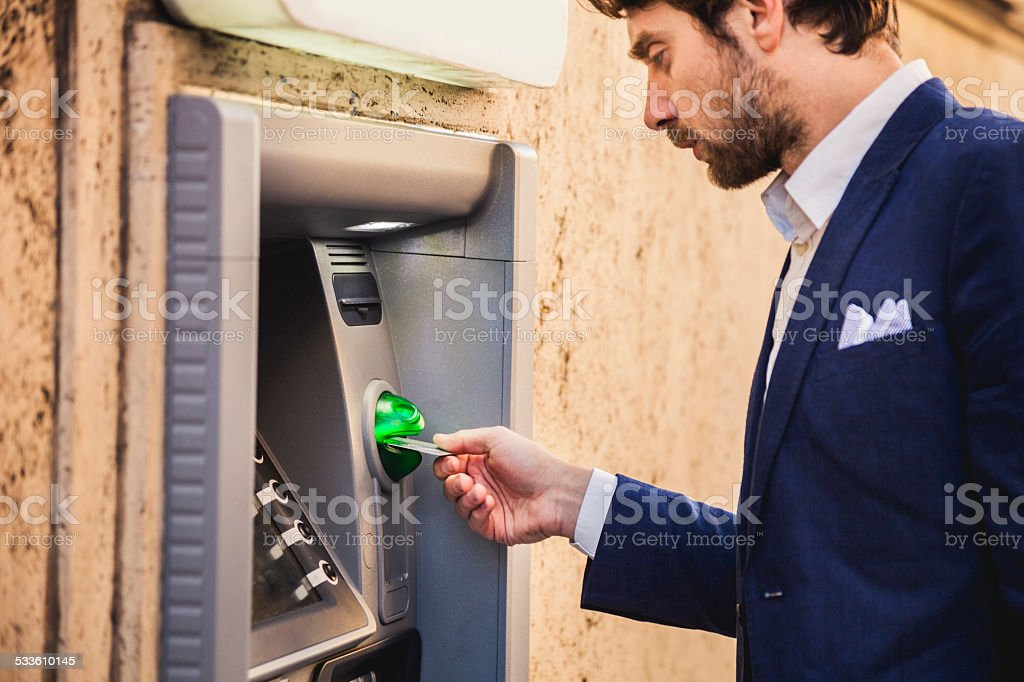 Man with credit card withdraw money stock photo