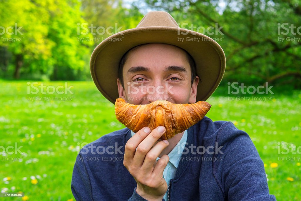 Man with croissant stock photo