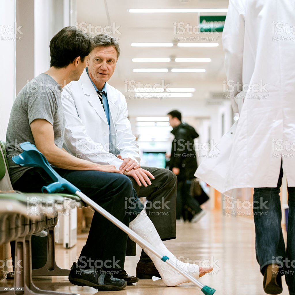 Man With Cruches And Cast On Broken Leg Consulting Doctor stock photo