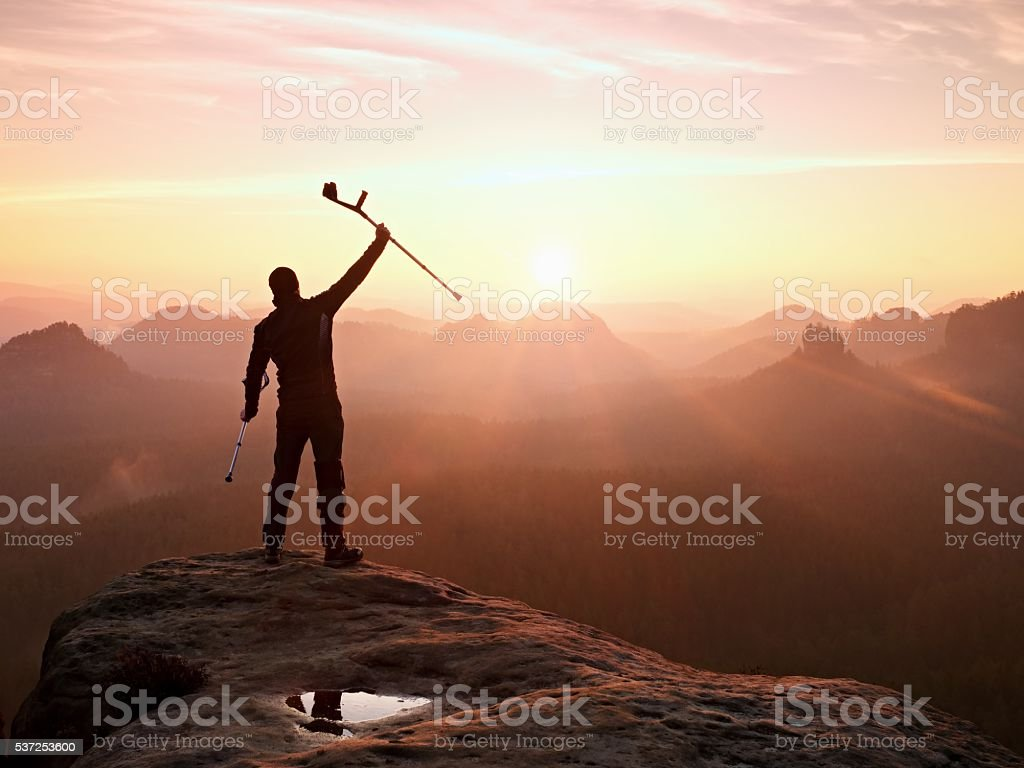 Man with  crutch  on mountain. Broken leg fixed in immobilizer stock photo