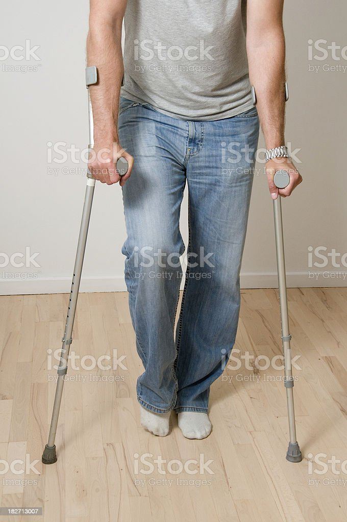 Man with crutches and an ankle or knee injury royalty-free stock photo