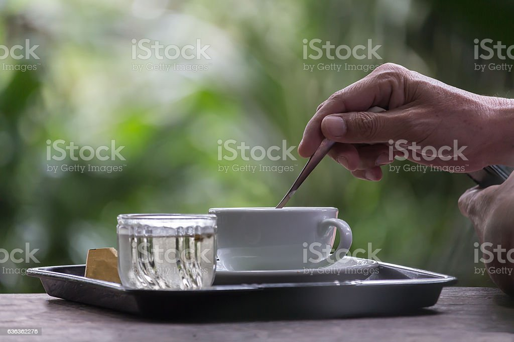 man with cup of coffee looking at outdoors stock photo