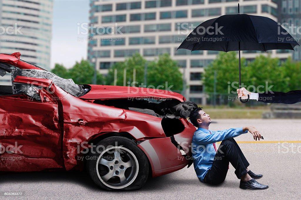 Man with damaged car sits under umbrella stock photo