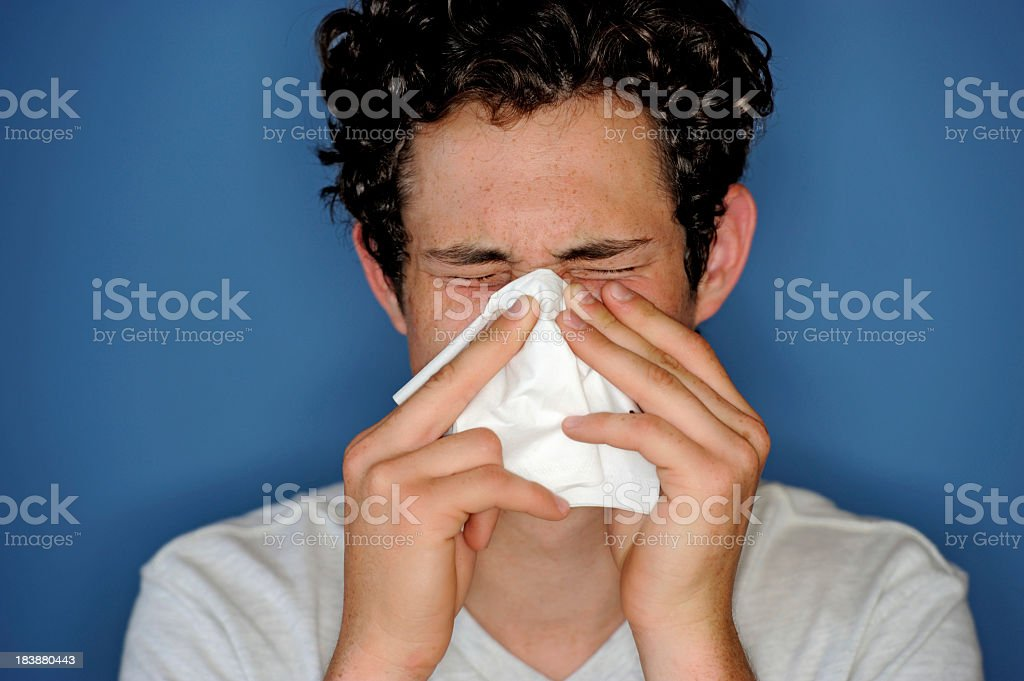 Man with dark curly hair blowing nose hard into white tissue royalty-free stock photo