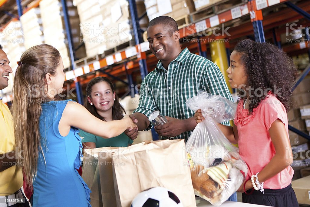 Man with daughter donating food and toys at charity drive royalty-free stock photo