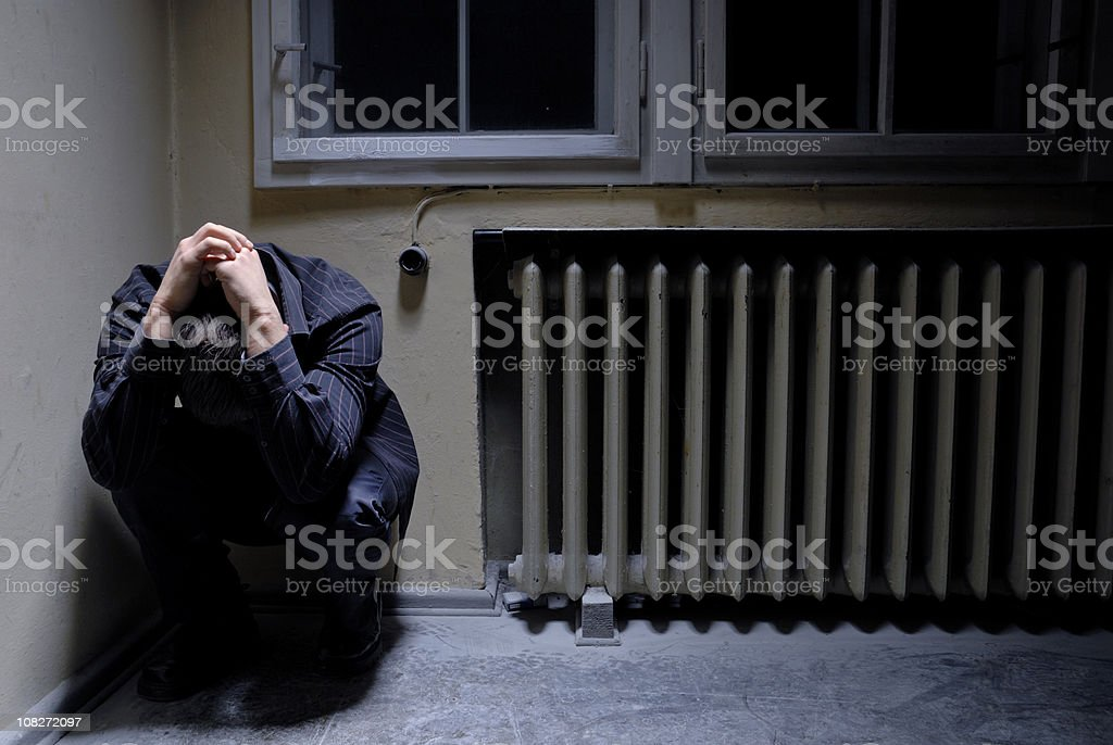 Man with deep depression in the corner of a room stock photo