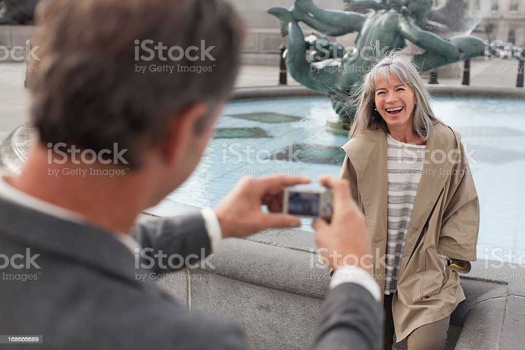 Man with digital camera photographing woman near fountain royalty-free stock photo