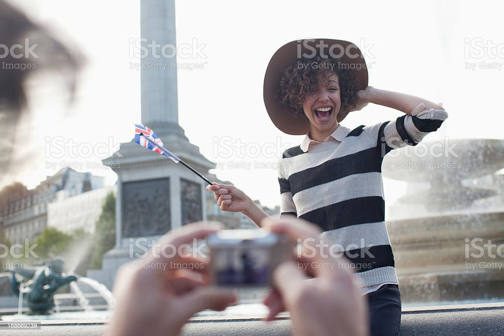 Man with digital camera taking photograph of happy woman with British flag in front of fountain royalty-free stock photo