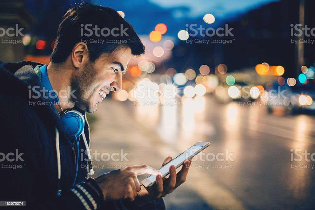 Man with digital tablet and headphones, outdoors at night traffic stock photo