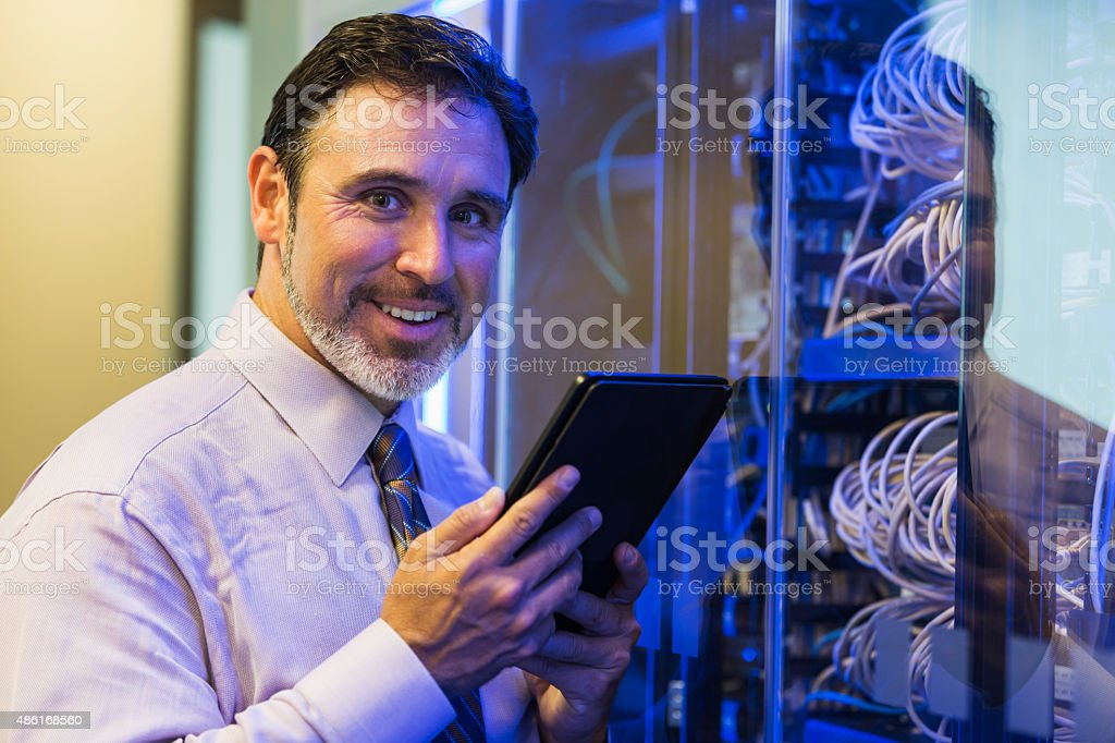 Man with digital tablet in server room stock photo