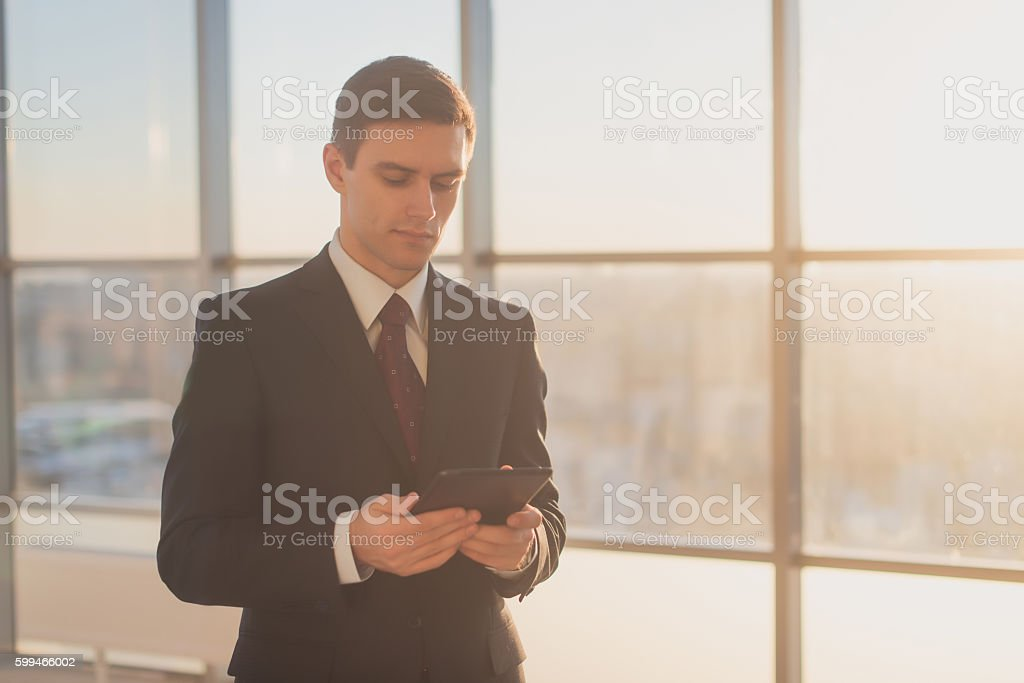 Man with digital tablet standing in modern office interior. stock photo