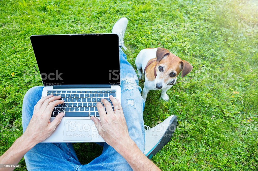 Man with dog and laptop stock photo