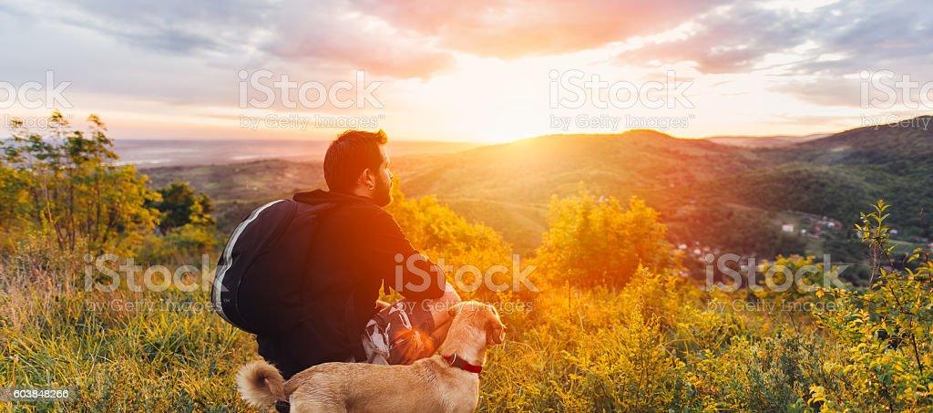 Man with dog enjoying mountain sunset stock photo