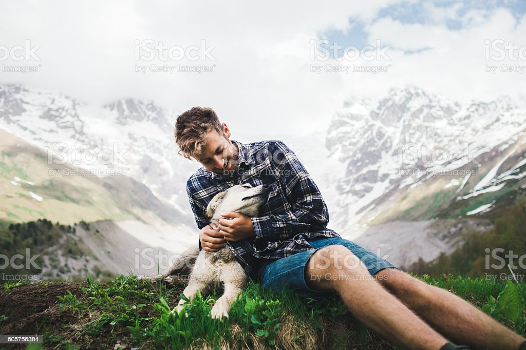 Man with dog in mountains stock photo