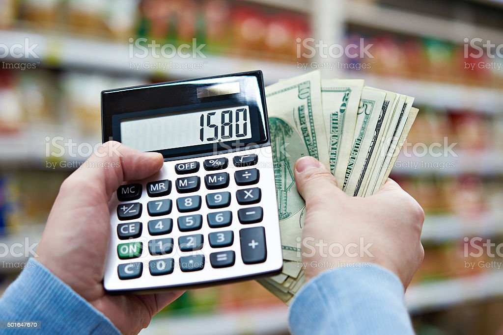 Man with dollars and calculator considers costs in store stock photo