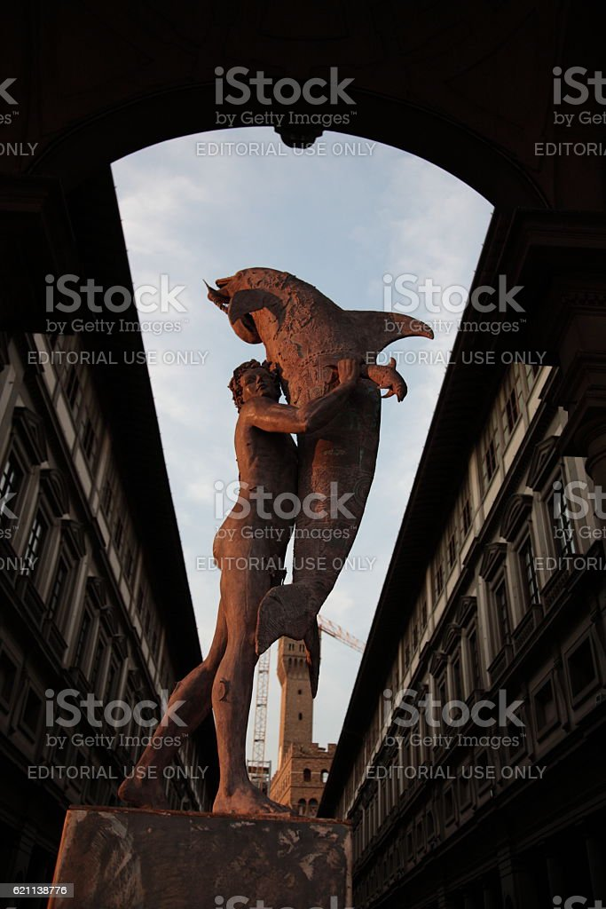 Man with dolphin statue and Uffizi Gallery in Florence, Italy stock photo
