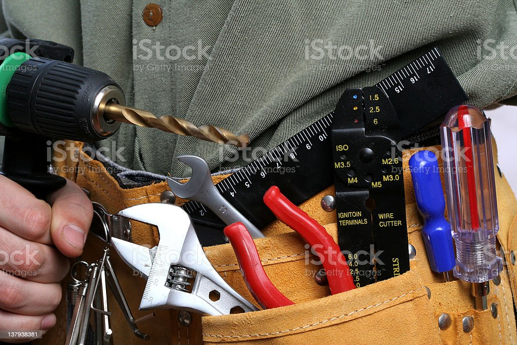 man with drill and tool belt stock photo