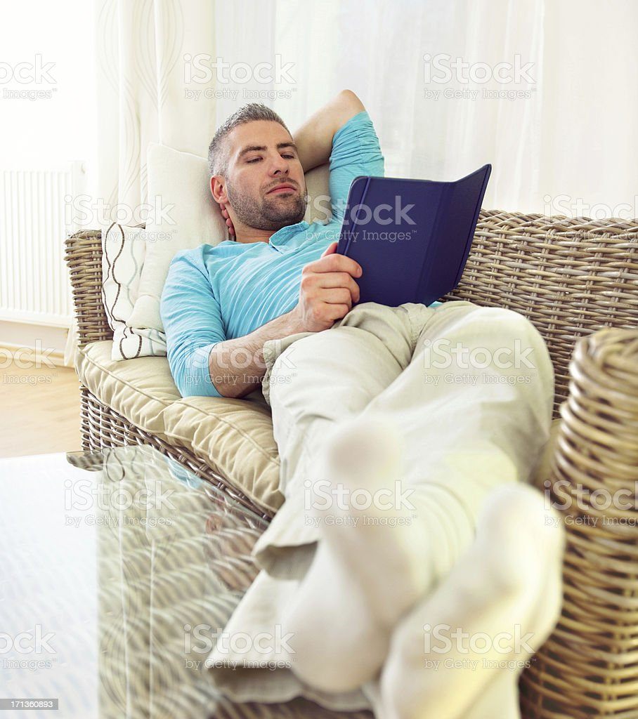Man with E-Reader on Couch at Home royalty-free stock photo