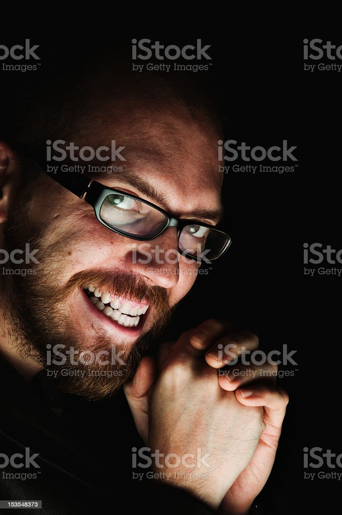 Man with evil look smiling beneath the shadows stock photo