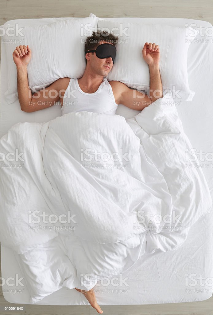 Man with eye patch lying in bed stock photo