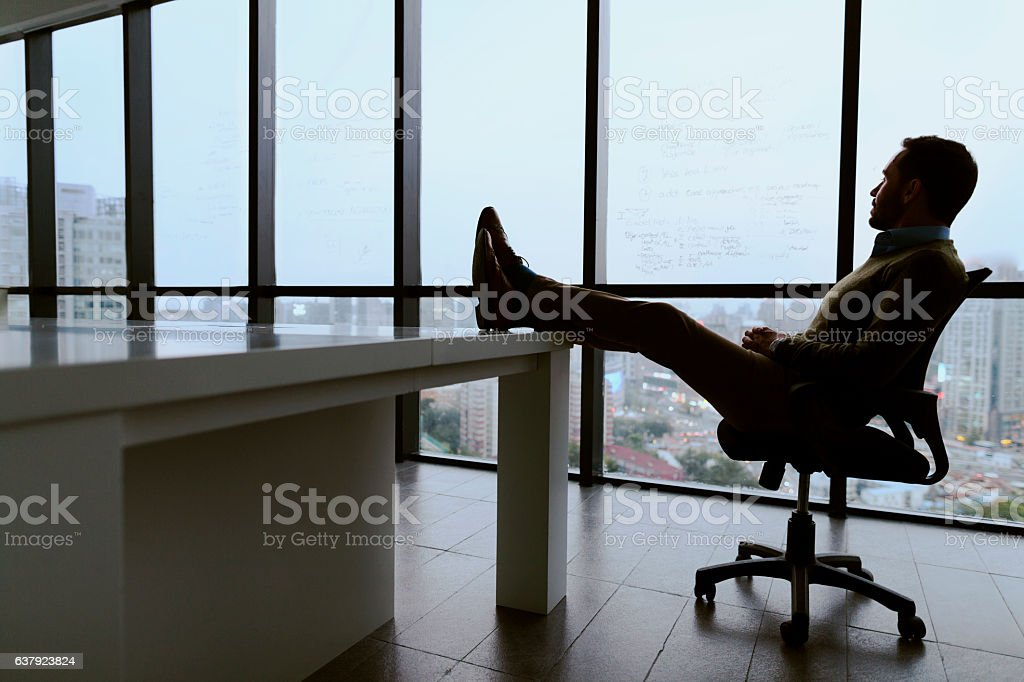 Man with feet propped up on table in meeting room stock photo