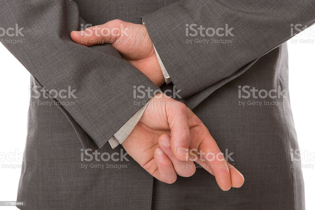 Man with fingers crossed behind back stock photo