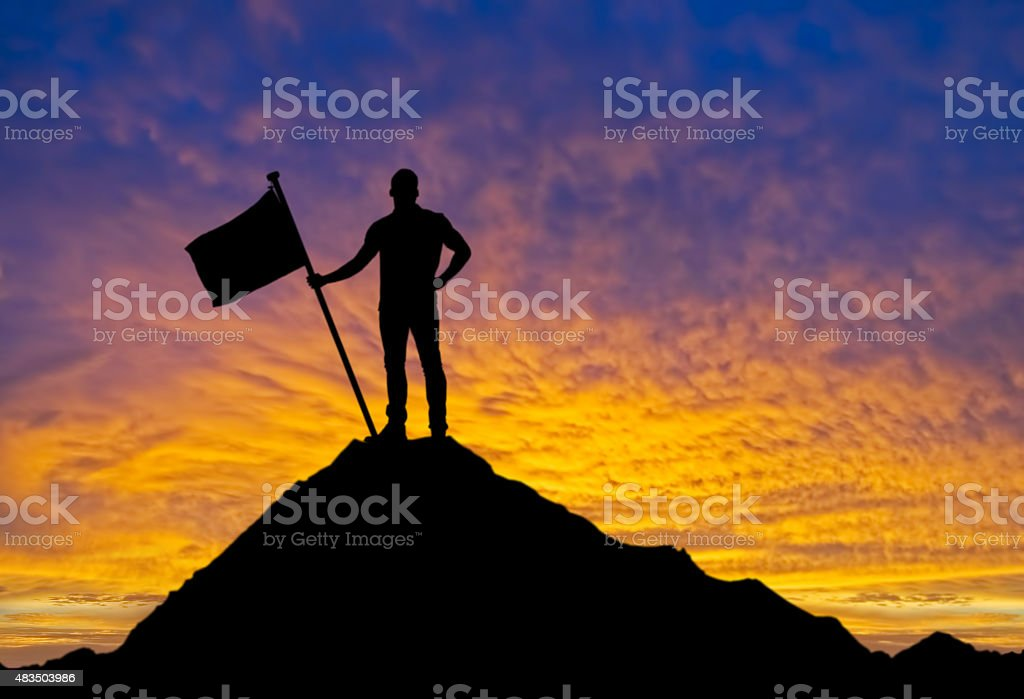 Man with flag standing on the top of mountain stock photo
