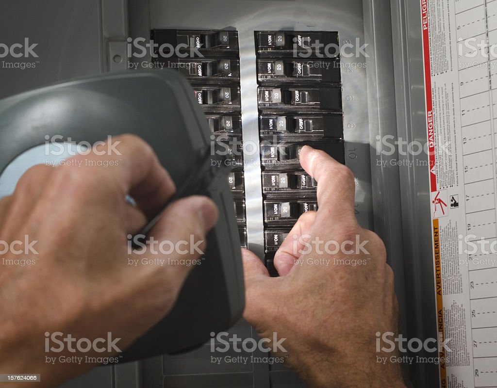 man with flashlight at residential circuit breaker panel stock photo