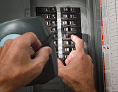 man with flashlight at residential circuit breaker panel