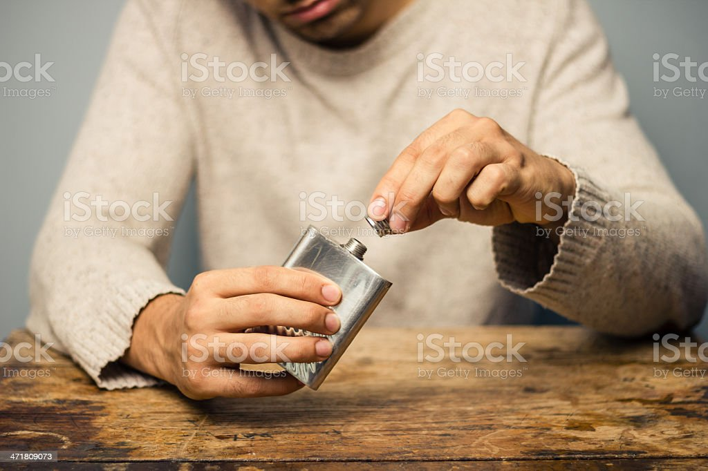Man with flask at table stock photo
